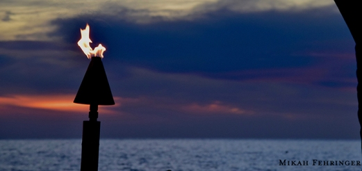 Flames flicker along the beachside casting eerie, but beautiful, shadows....